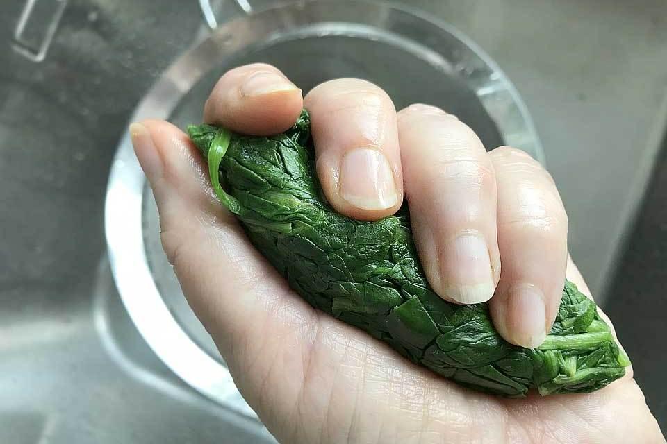 Den Spinat kurz blanchieren und das Wasser gut ausdrücken.