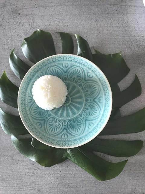 Den Jasminreis mit Hilfe eines Glas formen, kopfüber auf den Teller stellen und das Glas vorsichtig hochgeben. So entsteht ein hübscher Reiskegel.