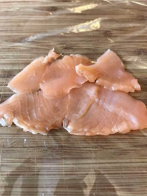 Die dünnen Lachsscheien werden für die Temari-Sushi nebeneinander auf die Foliegelegt.