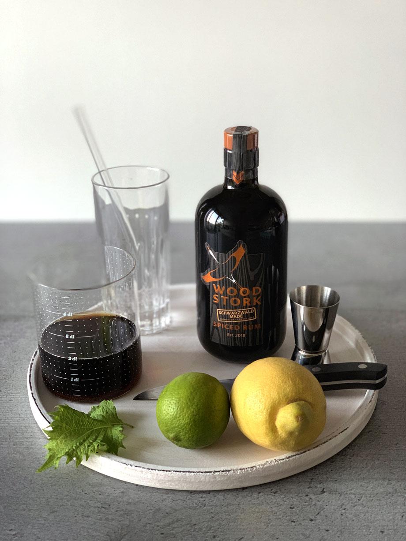 Die Zutaten für den Godjira Cuba Libre mit Wood Stork Spiced Rum: Cola, frische Shiso-Blätter, eine Limette, eine Zitrone sowie Wood Stork Spiced Rum.