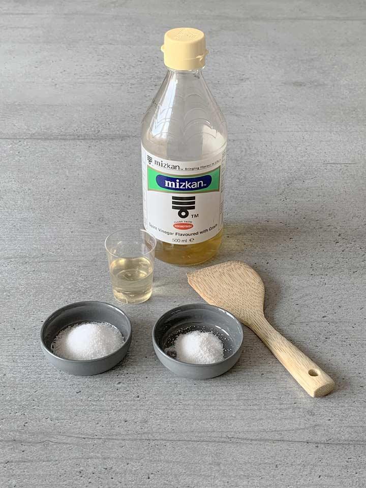 Sushi-Reis richtig säuern: der gekochte Reis wird mit einer Mischung aus Essig, Zucker und Salz gesäuert.