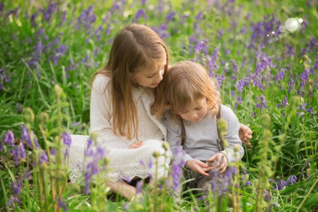 An older girl and younger boy sitting in the bluebells looking at a leaf the boy is holding - Spring Wood near Whalley