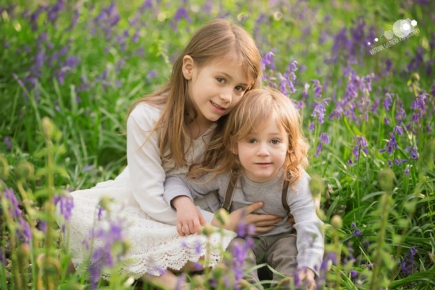 A older girl and younger boy sat together in the bluebells looking straight at the camera - - Spring Wood near Whalley