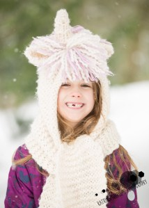 Bold Venture Park, Darwen - Portrait of a girl smiling to the camera missing one of her front teeth and wearing a wooly unicorn hood