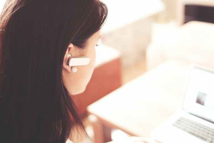 woman wearing earpiece using white laptop computer