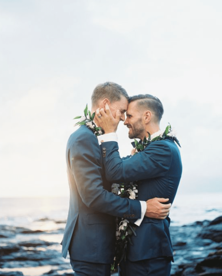 Gay friendly wedding photographer Sydney Australia two gay men holding each other with the ocean behind