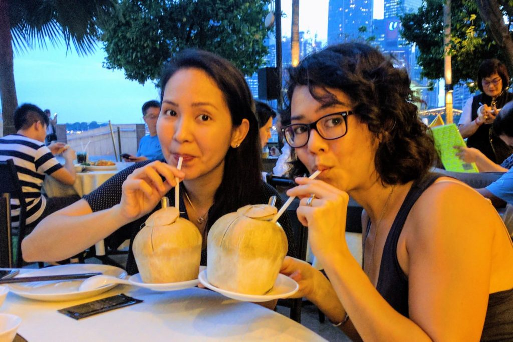 two women sipping coconut water through straws from fresh coconuts
