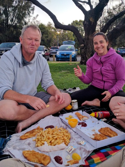 a couple eating fish and chips picnic style