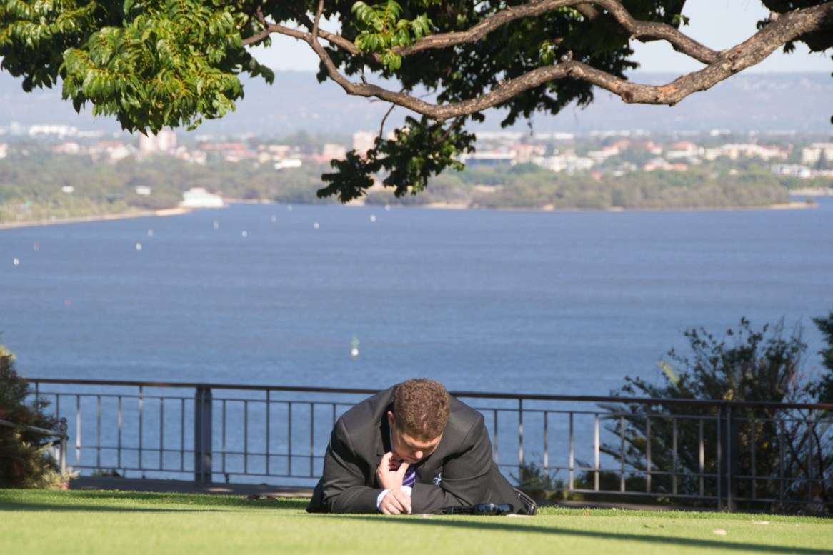 a guy in a business suit chilling out on the ground at a park