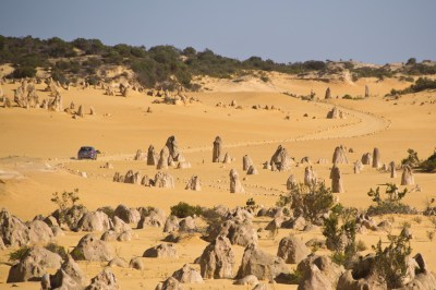 a car driving through a park of strange rock formations