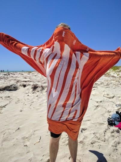 a towel blown against a body at the beach