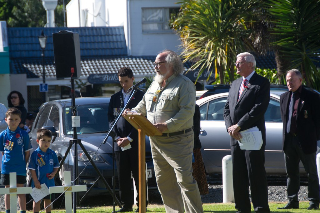 man speaking at outdoor ceremony