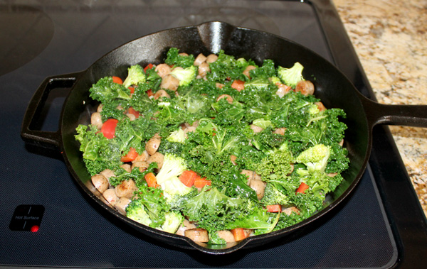 vegetables and sausage spread evenly in skillet