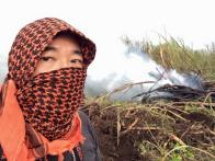 Photographer Baron Sekiya wearing a shemagh to filter out the smoke and ash on Maui at a cane fire.