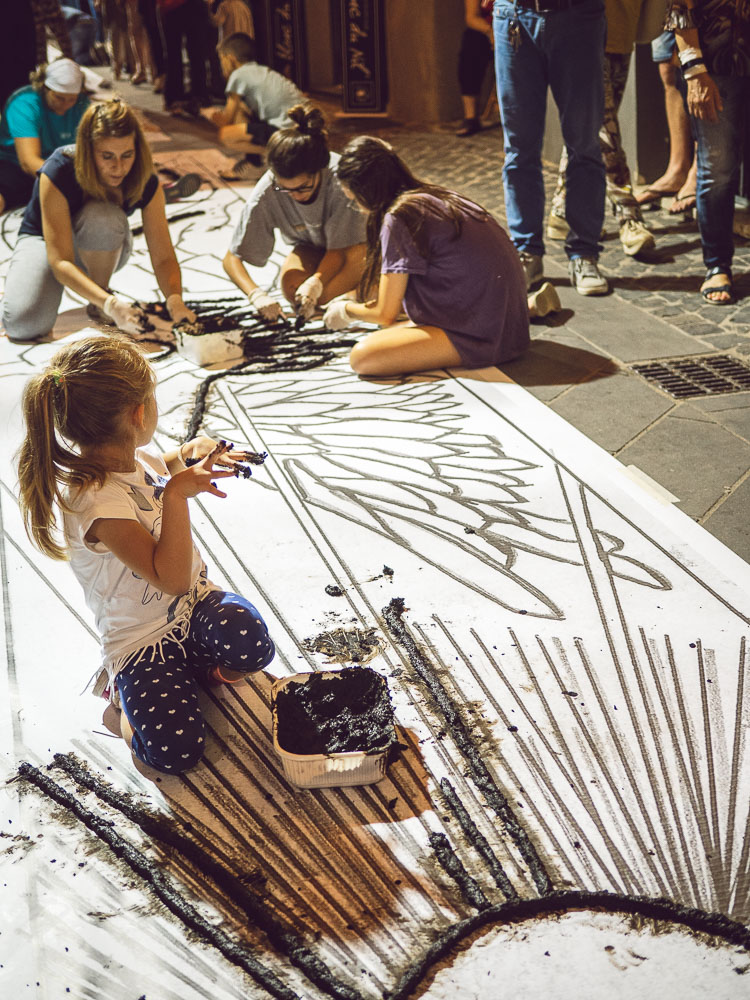 children working at the infiorata during the night