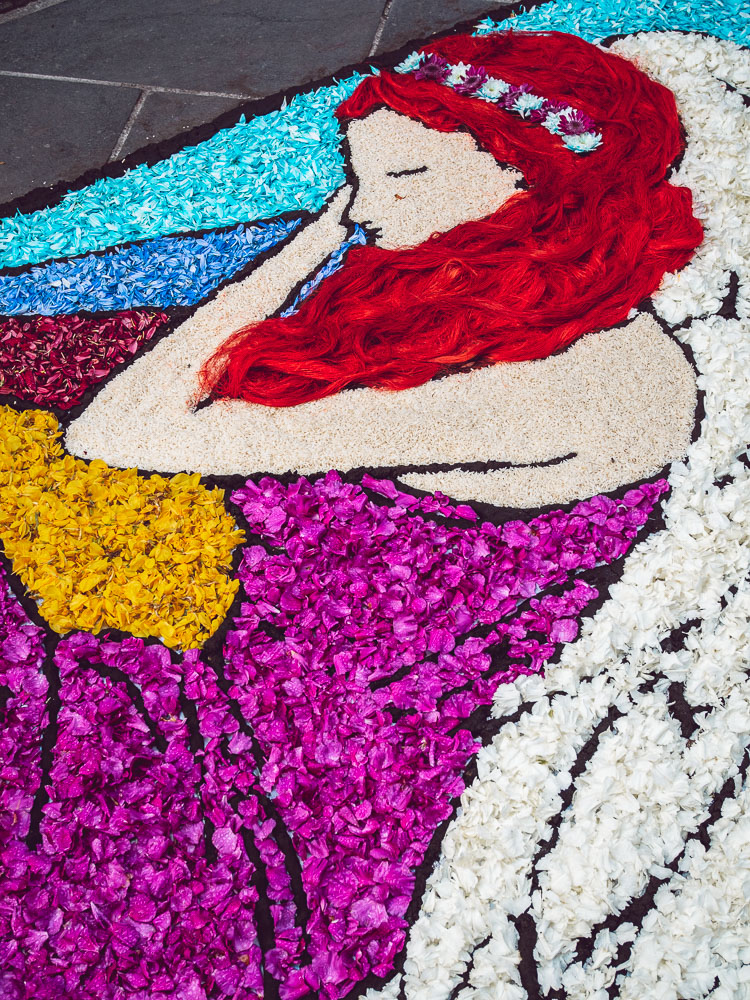 a lady with red hair drawn with flowers at the infiorata in bolsena