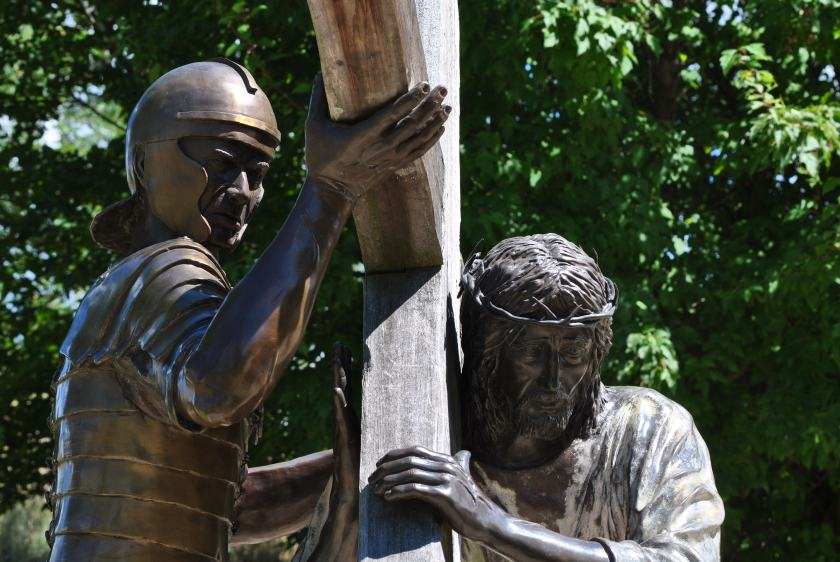 An armored soldier places the cross upon Jesus' shoulder.