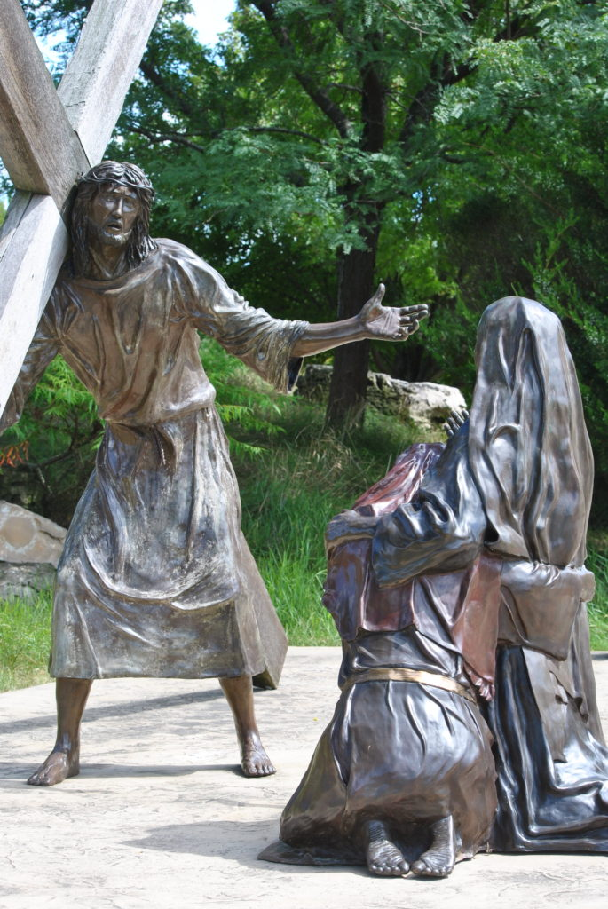 Two women from Jerusalem, on their knees weeping as Jesus passes by.