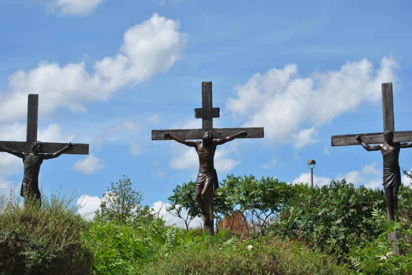 Three crosses, tall in the breeze, against a blue sky, Jesus in the middle.