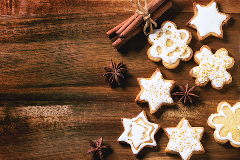 Christmas cookies with anise stars and cinnamon sticks over wooden background. Top view..