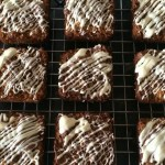 Individual flapjacks on a cooling rack with white icing decoration