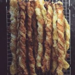 Cooked cheese straws on a cooling rack