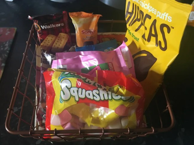 A basket of food including biscuits, chickpea crisps and sweets.