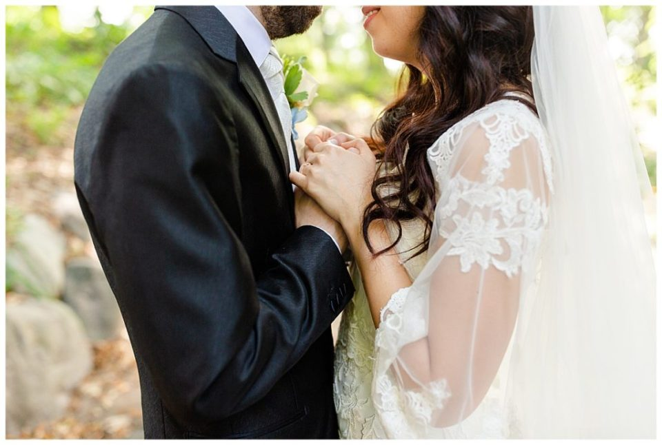 Bride in elegant lace wedding dress holding hands with groom