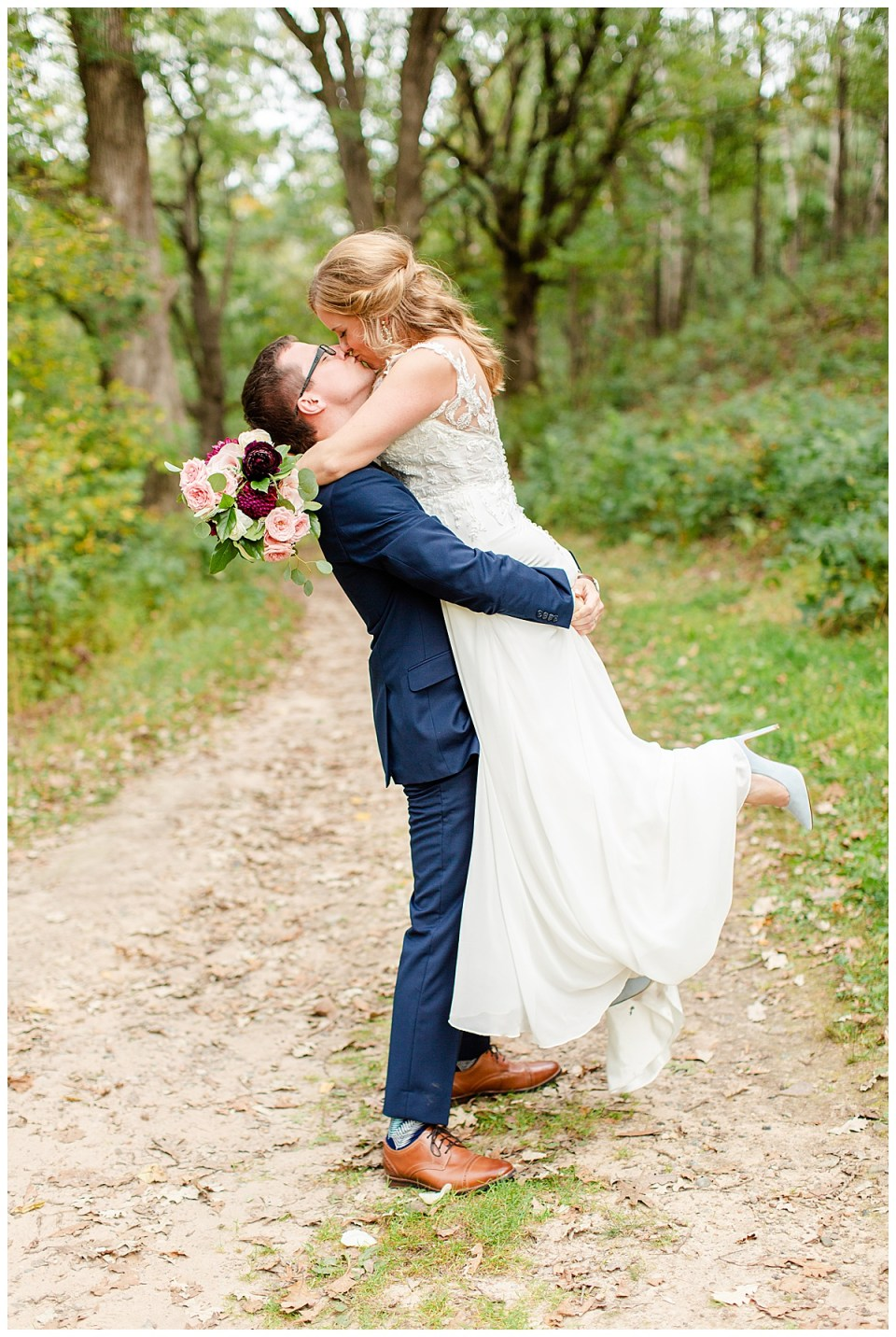 Romantic pose of bride and groom kissing at Lebanon Hills Park in Eagan, MN
