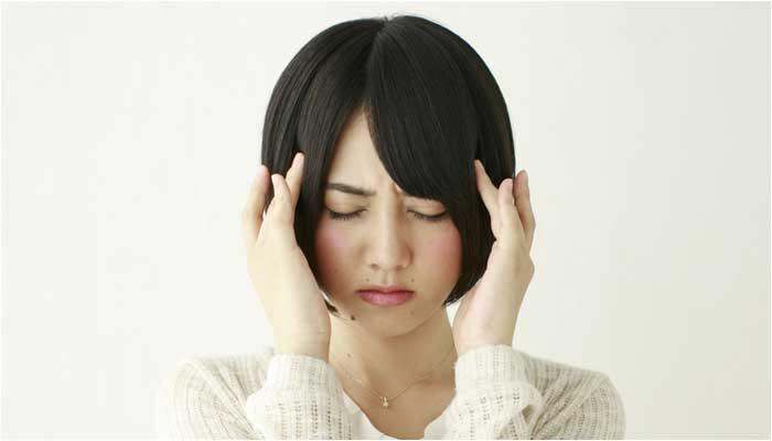 頭痛吐き気で悩む女性のイメージ画像