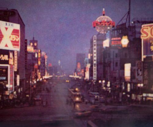 【33】ソニービル。流行発信するショールーム。1957年(昭和32年)、数寄屋橋に東京通信工業株式会社(後のソニー)がネオン広告塔を設置。トランジスタラジオ発売2年後の当時、初めて豆球を使用したネオン広告看板が話題になった。1959年(昭和34年)ショールームオープン。約20坪足らずのフロアに製品を並べた。「この銀座・数寄屋橋の一角を永久に確保し、多くの面での効果を永続的に得たいと考え、ここにソニービルを建設することになったのであります」と宣言し、1966年(昭和43年)ソニービルがオープン。芦原義信設計、グッゲンハイム美術館を参考に世界初『花びら構造』のユニークな建築様式を採用。正確さと装飾を廃した機能美、ビル自体がソニー製品であるかのように表現された。外壁に埋め込まれた2300個のブラウン管テレビ、パネルヒーティング、日本最高速エレベーターなど、新しい構想で話題をさらい1日平均2万人を超える盛況だった。その後、松下電器=テクニクス銀座ショールーム、日立製作所=Lo-Dプラザ、東京芝浦電気=東芝銀座セブン、日本ビクター=ニッパーズギンザが続き、日産自動車も銀座ギャラリーを開設した。【33】1960年(昭和35年)・銀座ネオン夜景