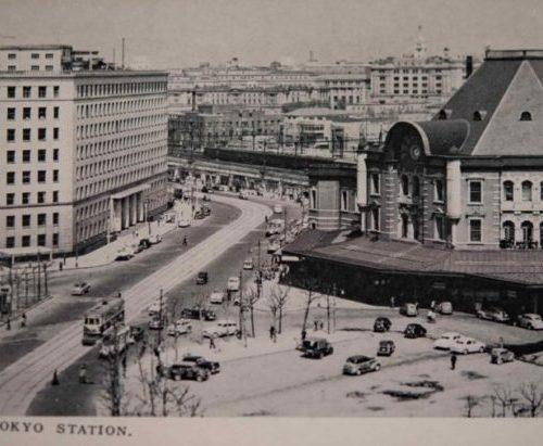 【35】帝都の象徴、東京駅。東京停車場(東京駅)は、日清戦争や日露戦争の停滞を経て、明治41年着工した。近代建築の父と呼ばれる辰野金吾が設計を手がけ、赤煉瓦と白い花崗岩を組み合わせた様式は「辰野式」と呼ばれる。1914年(大正3年)開業。コンクリートを多用したレンガ造のため、関東大震災では大きな損傷もなかったという。しかし1945年(昭和20年)の空襲で、耐火に優れた鉄骨煉瓦造の外観は残ったものの、ドーム屋根や内装はが焼失。戦災復旧工事で3階建駅舎が2階建にされ、焼失した壮麗なドームは八角形の寄棟となった。絵葉書の左に写るのは、今はなき旧国鉄本社ビル新館。1963年(昭和38年)竣工。新館は地上9階・地下3階で運輸省・国鉄本社の中枢が入った。ルネッサンス様式の優美な旧館は大戦中、空襲対策として1トン爆弾に耐える耐弾層を設置し、窓に木製の爆風避を設置し、外壁を迷彩塗装する工事が行われたという。【35】1963年(昭和38年)頃・東京名所東京駅