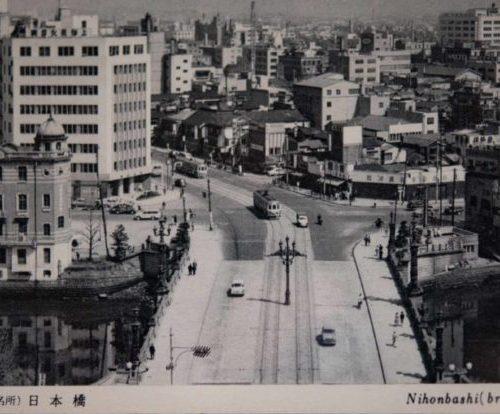 【32】国内諸街道の元標。日本橋は、中央区日本橋一丁目と室町一丁目との間にある日本橋川に架かるコンクリート造りの橋である。1603年(慶長8年)江戸幕府が開かれたとき日本橋、京橋一帯の新市街ができ、日本橋はそのとき初めて架けられたもので、翌年には日本橋を起点として諸街道の里程を定め、一里毎に一里塚が置かれた。1873年(明治6年)に「東京は日本橋。京都は三条の中央を以て国内諸街道の元標とす」と定められ、今も橋の中央に道路元標の鉄塔が建っている。現在の橋は1911年(明治44年)架け替えられたものである。1964年(昭和39年)東京オリンピックの前年、日本橋川を塞ぐように首都高速道路が建設され本来の景色を失ってしまった。戦災復興による道路整備が計画どおりに進まず、五輪へ向けて都心部の交通混雑を回避するため川や沿岸部などの空間を利用しての整備だった。その後、日本の高度経済成長を支える重要インフラとして活躍したが、すでに50年が経過して更新時期を迎え、景観を取り戻す署名運動も行われ、地下化が検討されている。【32】1955年(昭和30年)頃・(東京名所)日本橋