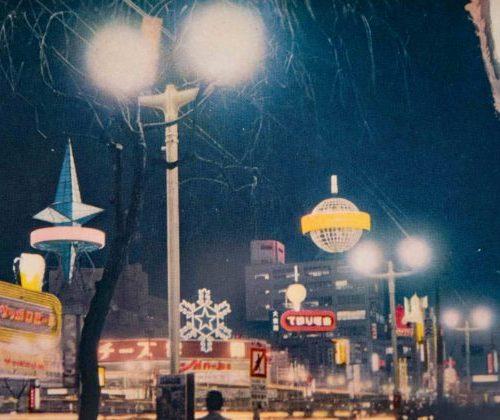 【31】ネオン広告塔が夜の銀座を照らす。銀座の夜を華やかに彩った高層ネオンは、1953年(昭和28年)晴海通りに面した不二越ビル(現在のアルマーニ銀座タワー)屋上に登場した森永ミルクキャラメルの広告塔。通称「サボテン」と呼ばれた地球儀。「ヒトデ型」のナショナル(現・パナソニック)は、当時3階建だった鳩居堂ビル屋上に、建物の2倍以上という巨大な大きさが話題に。銀座の名物になり、絵葉書や映画にも登場した。1963年(昭和38年)三愛ドリームセンターが完成すると目立たなくなって姿を消し、鳩居堂ビルも三愛と同じ高さのビルに改築された。雪印ネオンサインは、三愛ドリームセンタービルができる場所にあり、雪の結晶をまばゆく演出した。【31】1955(昭和30年)頃
