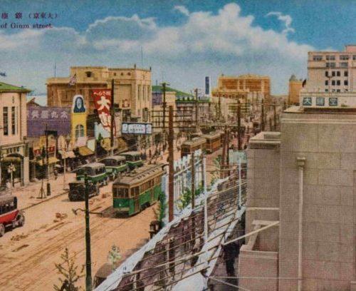 【27】街を往く人たちが、車窓の景色だった都電。1882年(明治15年)馬車鉄道が新橋〜日本橋間で開業、1903年東京電車鉄道と名を変え電化し、数寄屋橋〜神田橋間に東京市街鉄道が開業した。後に東京市電として公営化し、路線・系統の拡大がされた。絵葉書に描かれているのは昭和10年頃に登場したダーク・グリーンの車体。真鍮の金具を光らせていた。アール・ヌーボーの意匠が施された街路灯、 商店のショーウインドウにも電気のイルミネーションが使われ話題を集めた。1934年(昭和9年)、東京地下鉄道によって敷設された地下鉄(現在の東京メトロ銀座線)が銀座まで延伸し、1950年代より整備が急速に進み、西銀座駅の丸ノ内線が開業。その一方で自動車の増加に伴い、惜しまれつつも都電は昭和42年に廃止された。【27】1940年(昭和15年)頃・(大東京)銀座通り