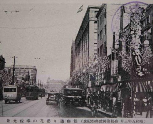 【13】バラック装飾から始まった復興建築。関東大震災からの復興建築 。焼け野原に出現したのは、仮設のバラックであった。仮店舗には「バラック装飾」と呼ばれる若い建築家達のアート運動が見られた。今和次郎が結成した「バラック装飾社」が有名で、住宅や商店などのバラックのファサードにペンキで絵を描くなどの活動を展開した。代表作である銀座のカフェ・キリンでは、怪獣のように口を開けたキリンを激しいタッチで描き、神田の東条書店には「野蛮人の装飾をダダイズムで」として、動物と渦巻き紋様を描いた。その後、復興が進みバラックの建設が減り活動も自然消滅した。彼らに対して、分離派建築会、芸術至上主義的な立場から厳しい批判に対し、今和次郎は世相風俗の表層的な部分にこそ宿る美の存在を主張した。現在『日本の近代建築(下)』岩波新書(1993)の中で、建築家 藤森照信氏は「モダンデザイン終了後のポストモダンの傾向の一つにほかならない」とその先進性を評価している。1930年(昭和5年)【13】(昭和五年三月 帝都復興式典祭記念)銀座通り櫻花の奉祝光景