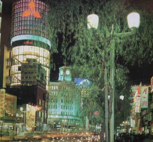 【38】高度経済成長期に始まった歩行者天国。1964年(昭和39年)東京オリンピックが開催され、1969年(昭和44年)GNP世界第2位となるなど、高度経済成長の時代に。1965年(昭和38年)完成した三愛ドリームセンタービル。リコー創業者市村清が戦後間もない1946年(昭和21年)旧六十九銀行跡地に2階建のビルを建設し、以後この地から経営拡大。法隆寺五重塔をヒントに「建物中心に大きな柱を立ててビル全体を総ガラス化させた円筒型のビル」を考案、名称も一般公募で決定した。外壁には社章である眼鏡のマークが配してあった。三菱電機スカイリングのネオンも長年親しまれた。その他にも、銀座最大を誇った東芝ビル、銀座ライオンビル、名鉄メルサ、資生堂ザ・ギンザなど、新しいビルが次々と建てられた。中央通りでは、1970年(昭和45年)歩行者天国が実施されるようになり休日の定番となる。【38】1970年頃・三愛ビルネオン、銀座和光と柳