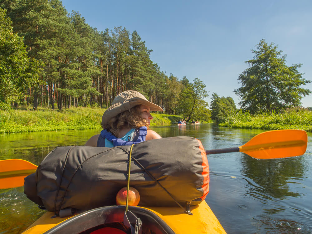 Woman on kayak with sun hat camping