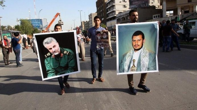 An Iraqi holds a portrait of Shiite Huthi rebels' leader in Yemen, Abdulmalik al-Huthi (R) and General Qassem Suleimani (L), the commander of the Quds Force AFP PHOTO