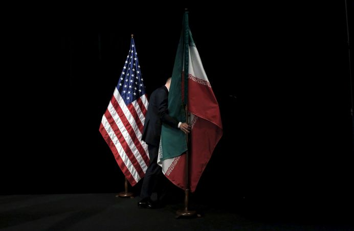 FILE PHOTO: A staff member removes the Iranian flag from the stage during the Iran nuclear talks at the Vienna International Center in Vienna, Austria July 14, 2015. REUTERS/Carlos Barria