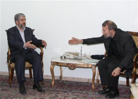 FILE PHOTO: Iranian Parliament Speaker Ali Larijani leans forward to shake hands with Hamas leader Khaled Meshaal (L) before a meeting at the Iranian embassy in Damascus. FILE PHOTO. REUTERS