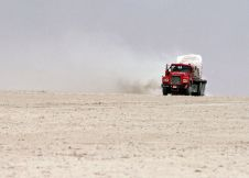 FILE PHOTO: A truck driver uses a shortcut across the dry bed of Bakhtegan Lake to carry stone from a quarry to market. REUTERS./