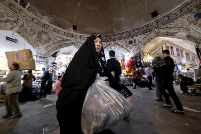 A woman walks with her purchased goods at the Grand Bazaar in central Tehran. REUTERS