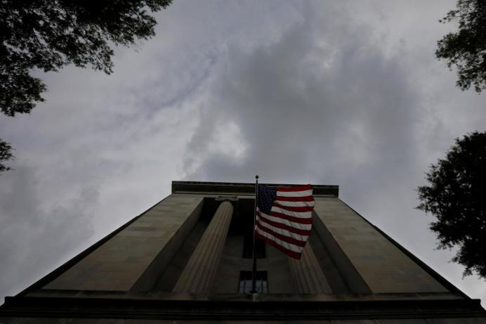 FILE PHOTO: A U.S. flag flies at the headquarters of the Department of Justice in Washington, U.S. REUTERS/Brian Snyder