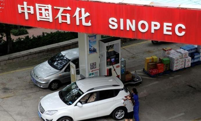 A customer gets the tank of her car filled at a Sinopec gas station in Qingdao, Shandong province, China.REUTERS