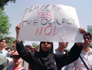 FILE PHOTO: A student from Tehran university holds a placard calling for democracy in Iran. Reuters