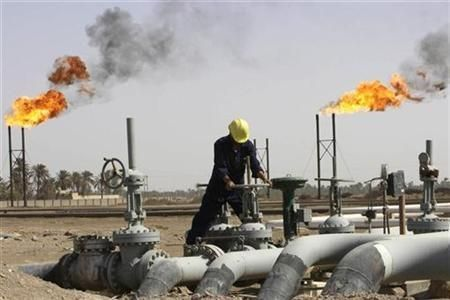 FILE PHOTO: An Iraqi worker maintains an oil pipe at Nahr Al-Umran gas refinery in Al-Dier District, northern Basra. Reuters
