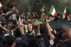 FILE PHOTO: Students show victory signs and red roses during protests in central Tehran December 7, 2009. REUTERS