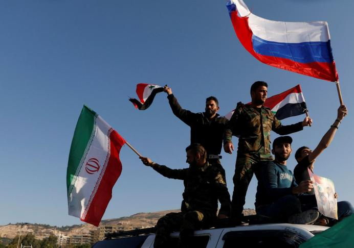 Syrians wave Iranian, Russian and Syrian flags during a protest against U.S.-led air strikes in Damascus,Syria April 14,2018. REUTERS/ Omar Sanadiki