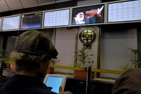 FILE PHOTO: An investor looks at a tablet supplying stock market information about listed companies on the Tehran stock exchange in Tehran, Iran. REUTERS